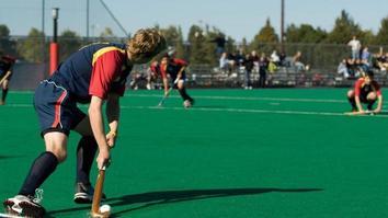 University students playing hockey on a hockey turf