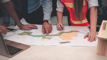 People around a table looking at a design drawing, with a laptop nearby