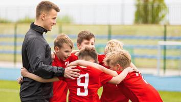 Adult teacher huddled with a few children from a football team wearing red jerseys